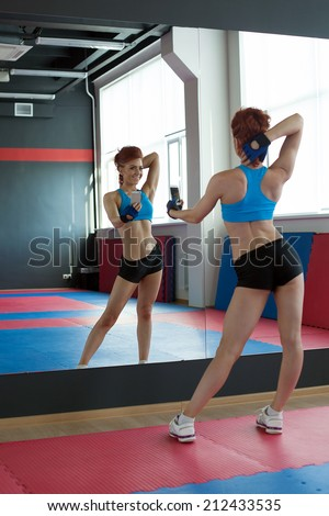 Slim girl photographing herself in fitness center - stock photo