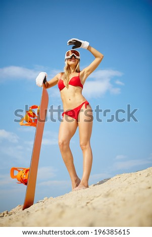 Slim girl posing with snowboard on the beach waiting for winter season - stock photo