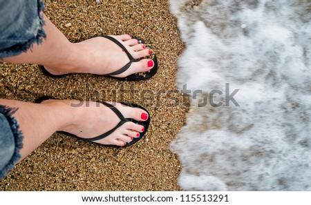 slim girl's legs on sandy beach - stock photo