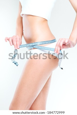 Slim girl with centimeter measuring her slim beautiful body. - stock photo