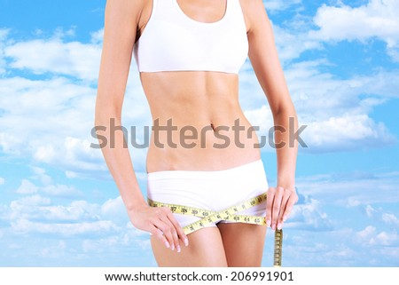Slim girl with tape on sky background - stock photo