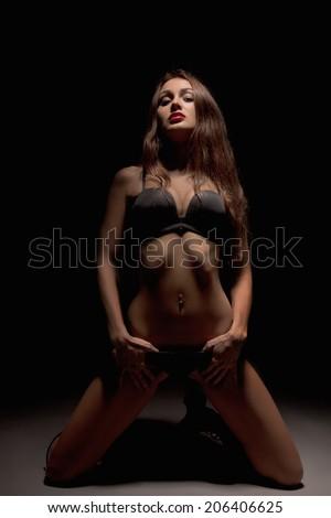slim luxury girl in lingerie on knees at dark low key - stock photo