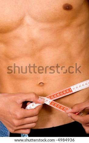 slim man measuring himself - lose weight series - stock photo