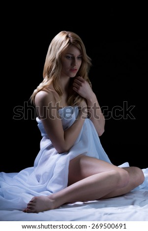 Slim naked sensual girl sitting alone in bed - stock photo