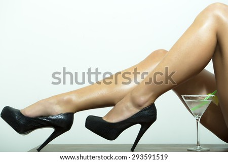 Slim naked sexy female legs in black leather shoes on high heels and cocktail with lime in glass on white background, horizontal picture - stock photo