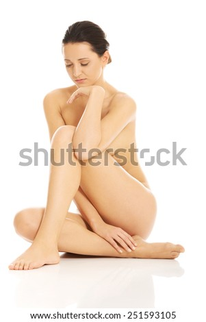 Slim nude woman sitting on the floor