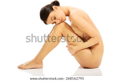 Slim nude woman sitting with her head on knees.