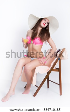 slim pretty girl in a bikini, big hat and sunglasses, sitting in a chaise lounge and drinks a cocktail from a glass - stock photo