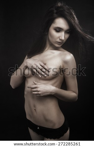 slim pretty naked girl cover her beautiful bared breast on black background monochrome toned image - stock photo