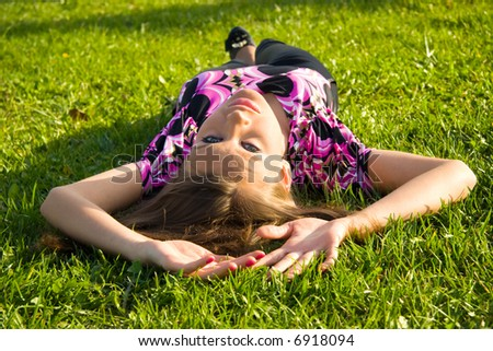 Slim sexy girl on a green grass. - stock photo