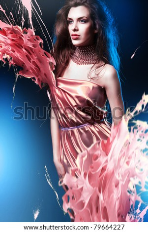 slim sexy woman in pink dress with long hair and paint splash - stock photo