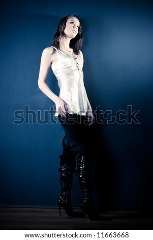 Slim sexy woman on dark background. Soft yellow and blue tint. - stock photo