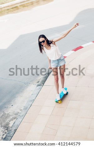 Slim sporty young beautiful woman in white t-shirt, short jeans shorts and trendy sunglasses ride blue longboard skate board. Urban scene, city life. Cute attractive sexy hipster girl have fun.