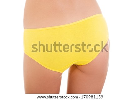 Slim tanned woman's body in yellow panties. Isolated over white background.