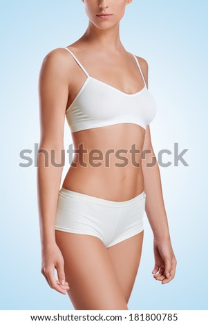 Slim tanned woman's body. Isolated over white background. - stock photo