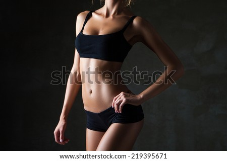Slim tanned woman's body  over dark grey background - stock photo