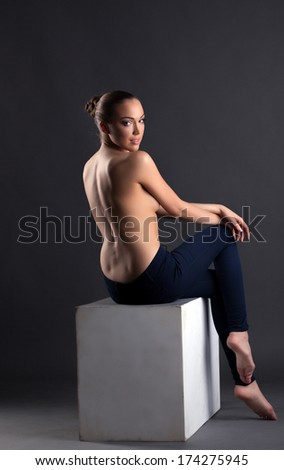 Slim topless girl sitting on cube, back to camera