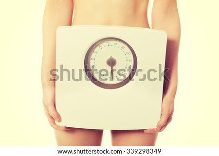 Slim undressed woman holding a scale.