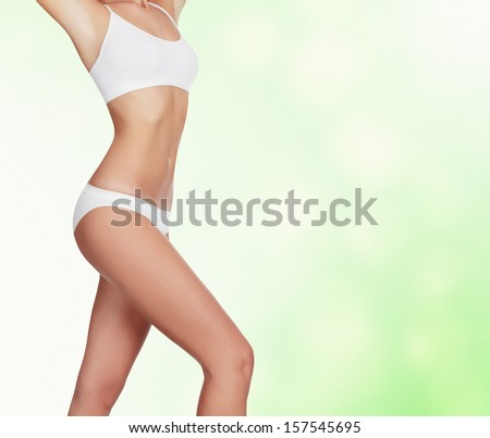Slim woman against an abstract green background with circles and copyspace  - stock photo