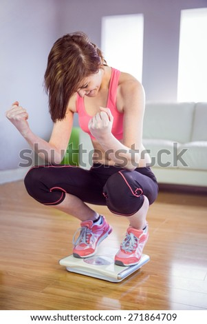 Slim woman cheering on scales in front a sofa - stock photo