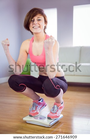 Slim woman cheering on scales in front of a sofa