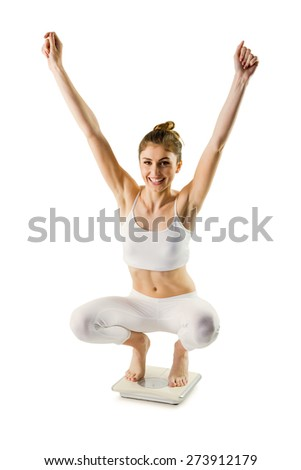 Slim woman cheering on scales on white background - stock photo