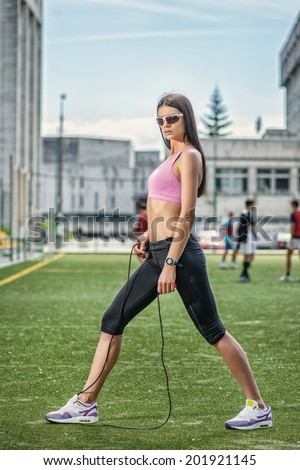 Slim woman doing fitness and aerobics on the football field between the football team and athletes and making stretching rope - stock photo