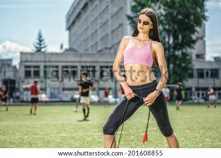 Slim woman doing fitness on the football field between the football team and athletes - stock photo