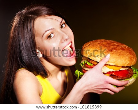 Slim woman eating hamburger. - stock photo