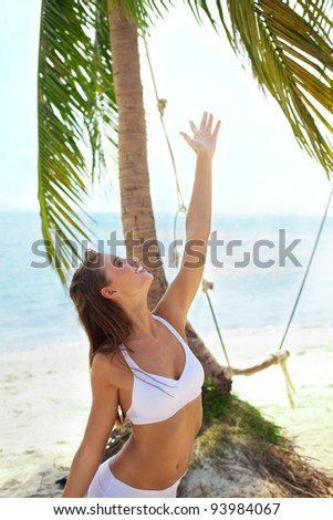 Slim woman enjoyed  exotic environment, under the palm tree at sea background - stock photo