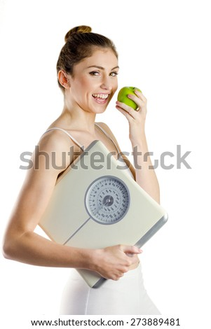 Slim woman holding scales and apple on white background