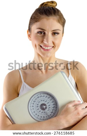 Slim woman holding weighing scales on white background - stock photo