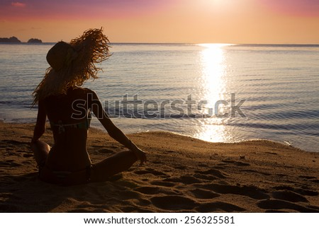 Slim woman in big hat is sitting on the beach and looking to the sunset - stock photo
