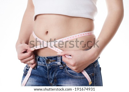 Slim woman in jeans measure waist with tape. - stock photo