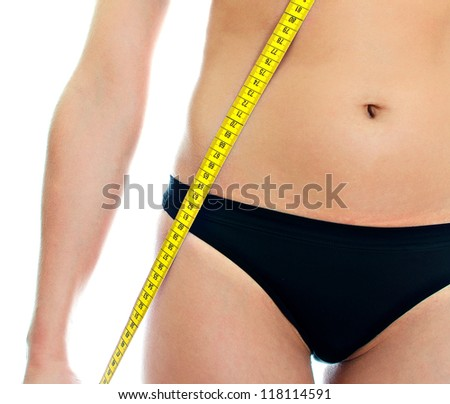 Slim woman in underwear holding measure tape . Isolated on white