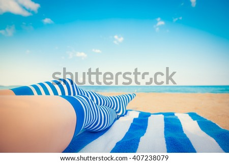 Slim woman legs on a beach. Summer vacation and travel concept. Shallow depth of field
