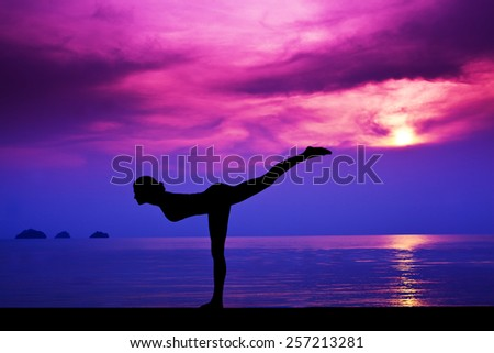 Slim Woman making yoga on the beach in the sunset