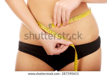Slim woman measuring her waist. - stock photo