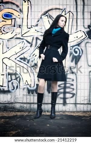 Slim woman on graffiti wall background. - stock photo