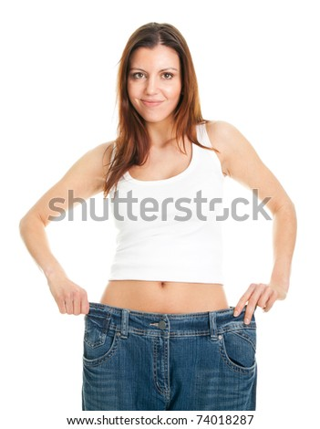 Slim woman pulling oversized jeans - stock photo