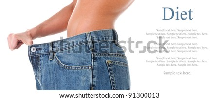 Slim woman pulling oversized jeans. Diet concept. Isolated on white - stock photo