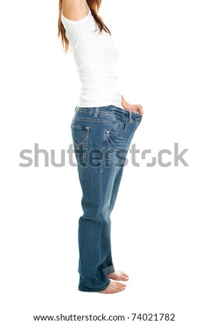 Slim woman pulling oversized jeans. Weight loss concept. Isolated on white - stock photo