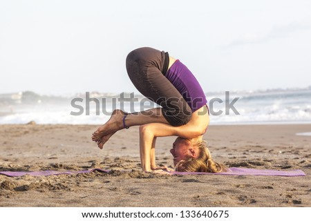 Slim woman standing on her head  doing yoga �upside down - stock photo