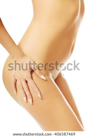 Slim woman touching her naked thigh - stock photo