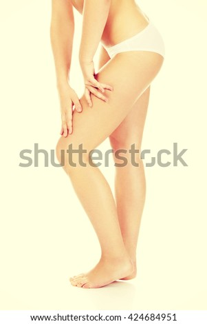 Slim woman touching her thigh - stock photo