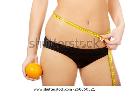 Slim woman with apple measuring her waist. - stock photo