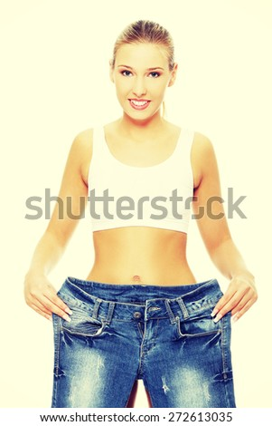 Slim woman with too large jeans - stock photo