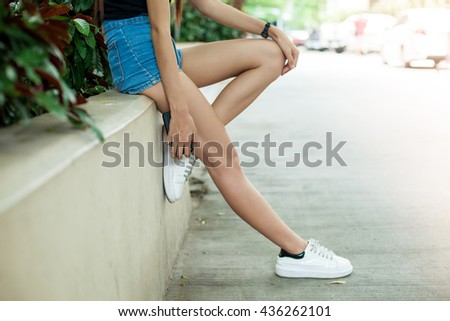 slim young girl sit on the wall waiting with her mobile