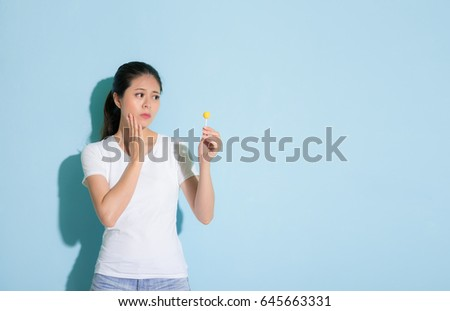 slim young lady holding and looking at lollipop candy worried about dental problems and touching sensitive tooth position in blue wall background.