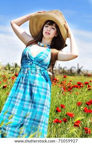 slim young woman standing in poppy field over the blue sky - stock photo